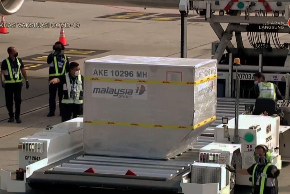 KUMPULAN pertama vaksin Covid-19 Pfizer-BioNTech dibawa keluar oleh petugas MasCargo dari Pesawat Airbus 330-300 MAS selepas tiba di KLIA. FOTO ihsan RTM