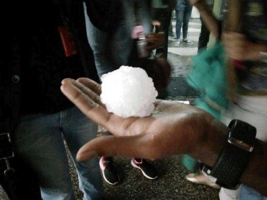 Orang ramai menunjukkan hujan batu yang dikutip semasa ribut di Bukit Jalil 3 Jun lalu. - Foto hsan Pembaca